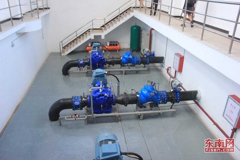 """取水泵站安装了三台水泵(东南网记者 卢金福 摄) 福建向金门地区供水工程设计流量为3.4万m3/d,远期5.5万m3/d。工程由取水泵站、陆地输水管道和跨海输水管道三部分组成。记者在福建晋金供水有限公司看到,取水泵站安装三台水泵,总装机容量330kW。 福建水投集团副总经理朱金良告诉记者,""""晋金供水""""工程通过取水口抽水,水通过水泵站的机组时进行加压,电能转成机械能,这样水就能够通过管道送到金门。""""晋江和金门的水平差不多,水是无法自然流过去的,要靠水泵增压抽过去,这相当"""